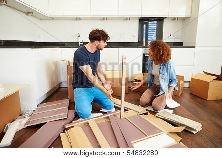 Couple Putting Together Self Assembly Furniture In New Home