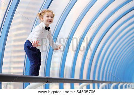 Little cute red hair girl balances on handrail in gallery near window. poster
