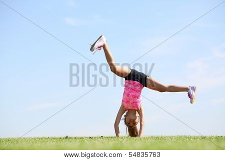 Little beautiful girl somersaults on green field at sunny day.