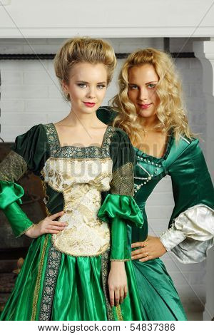 Two beautiful women in green medieval costumes stand near chimney with boiler.