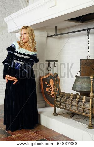 Blonde woman in medieval costume poses near fireplace and looks away.