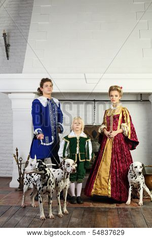 Father, mother and son in bright medieval costume stand near fireplace with three dalmatians.