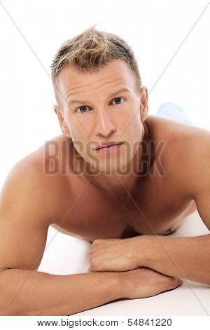 Grown man without shirt posing in studio