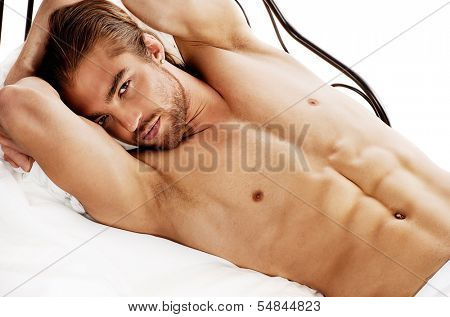 Handsome nude man lying in a bed. Isolated over white. poster