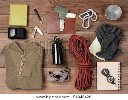 Overhead view of gear laid out for a backpacking trip on a rustic wood floor. Items include, rope, gloves, sweater, carabineers  book, belt, cup, passport, wallet, canteen, compass, money, map, knife