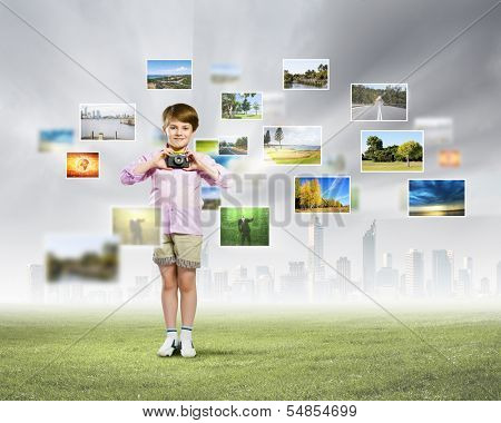 Image of cute boy holding photo camera standing among photos