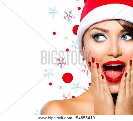 Christmas Woman. Beauty Model Girl in Santa Hat isolated on White Background. Funny Laughing Surprised Woman Portrait. Open Mouth. True Emotions. Red Lips and Manicure. Beautiful Holiday Makeup.  poster