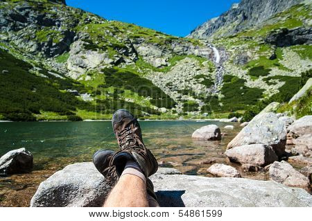 Hiker resting over the glacier lake