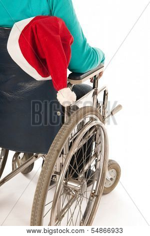 Person riding in wheelchair with Christmas hat from Santa Claus