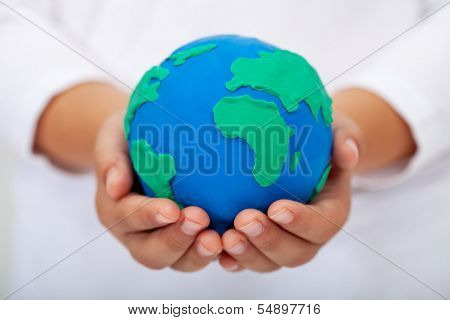Our home - child holding earth globe made of clay
