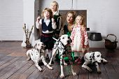 Beautiful woman in medieval costume with three children and three dalmatians wonder near chimney.  poster