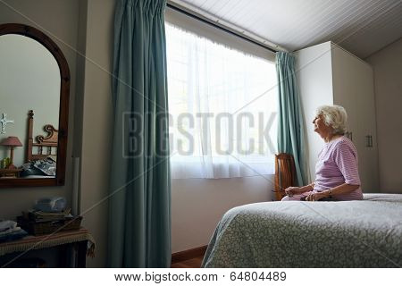 A depressed elderly widow sitting on her bed looking out the window