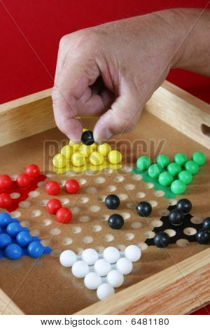 Close up of hand moving Chinese checkers piece