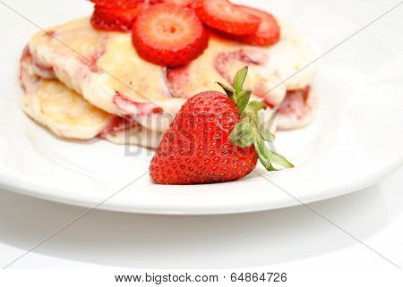 A Ripe Strawberry In Front Of Fruity Hotcakes
