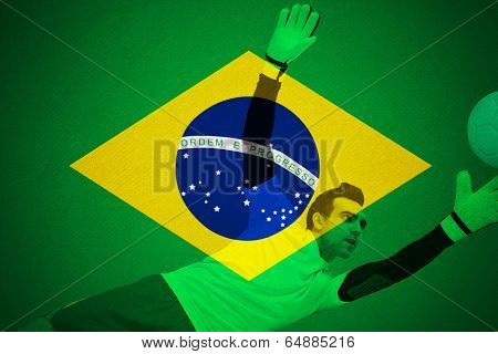 Goalkeeper in yellow making a save against football in brazilian colours poster