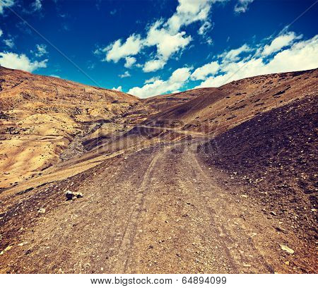 Vintage retro effect filtered hipster style travel image of dirt road in mountains (Himalayas). Spiti Valley,  Himachal Pradesh, India