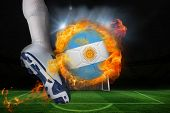 Football player kicking flaming argentina flag ball against football pitch and goal under spotlights poster