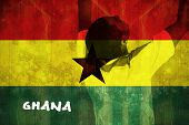 Excited handsome football fan cheering against ghana flag in grunge effect poster