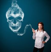 Pretty young woman smoking dangerous cigarette with toxic skull smoke  poster