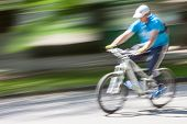 cyclist in traffic on the city roadway. Intentional motion blur poster
