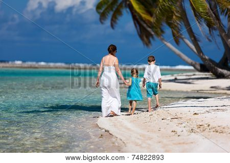 Back view of a mother walking with her two kids at tropical island