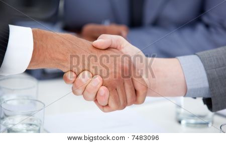 Close-up of confident business people closing a deal in a company poster