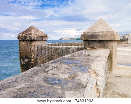 The famous Malecon seawall in Havana with El Morro castle on the background