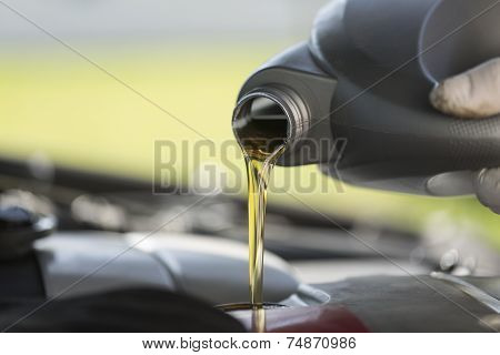 Fresh oil pouring into a car engine during service