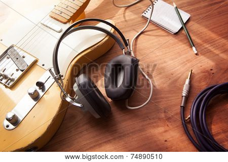 Guitar recording scene. An electric guitar, memo pad , and a professional grade headphones on a rustic or bare wooden table, with by-the-window type warm light coming in. poster
