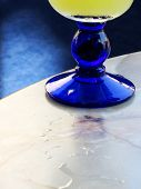 A blue glass of juice on a table. poster