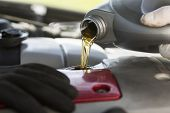 Fresh oil being poured during a car service poster