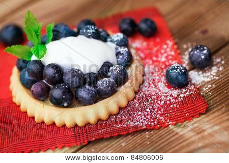 Blueberry  on a biscuit with creme on wooden background