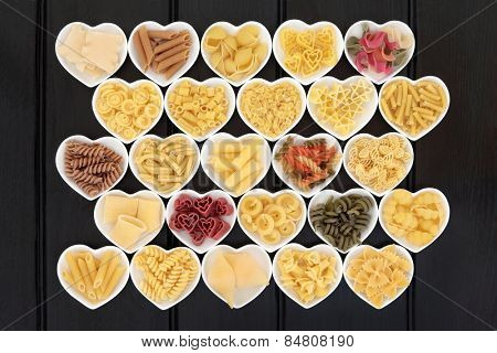 Italian pasta dried food selection in heart shaped porcelain dishes over dark wood background. poster