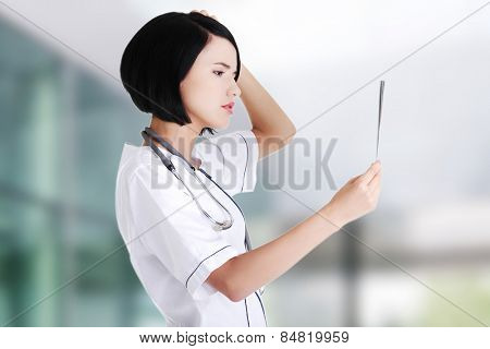 Beautiful female doctor analysing x-ray
