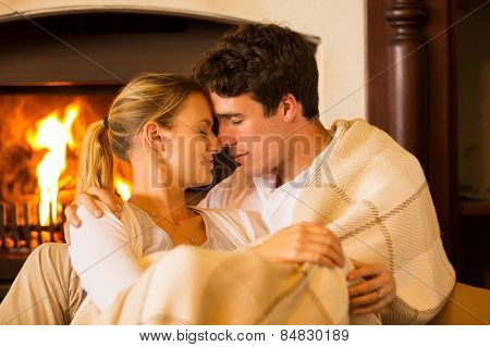 affectionate young couple in love cuddling near fireplace