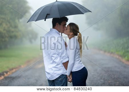 loving young couple in love under umbrella in the rain