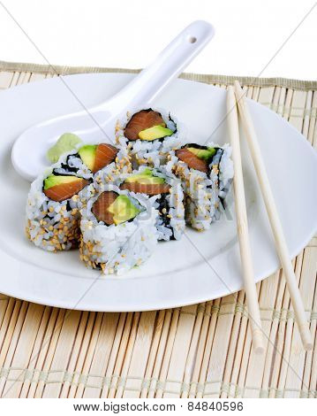 Raw fish and avocado sushi on a white plate with chopsticks and wasabi poster