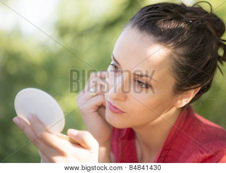 Beautiful Woman Loking In Her Pocket Mirror