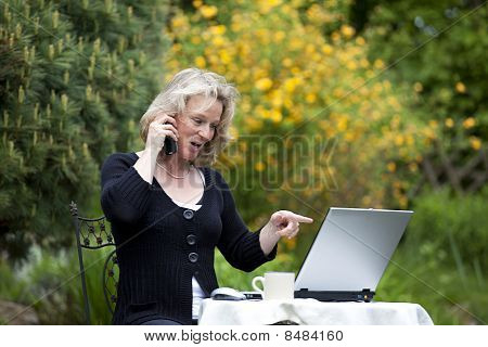 blond woman pointing at laptop