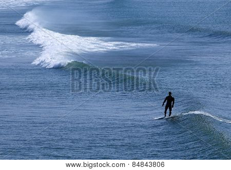 Anonymous lonely surfer on a surfboard and wave