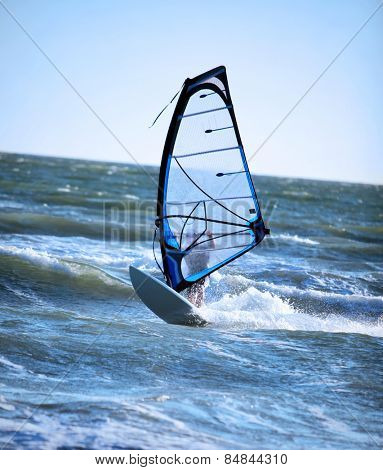 Lone anonymous windsurfer in the ocean catching a wave