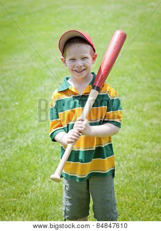 Cute boy with big smile outdoors on with baseball bat portrait