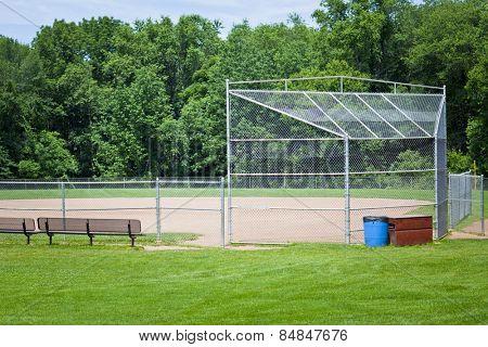 Empty baseball pitch with woodland background