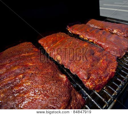 BBQ ribs cooking on a hot grill