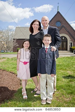 A family dressed smartly outside a church