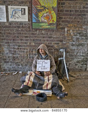 LONDON, UK - AUG 22, 2014: Homeless man with an asking for help sign sleeping in tunnel outside Waterloo train station in London.