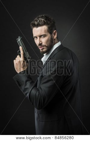 Confident undercover agent with a gun against dark background poster