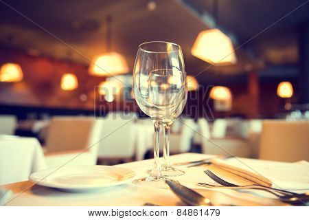 Served dinner table in a restaurant. Restaurant interior. Cozy restaurant table setting. Defocused background