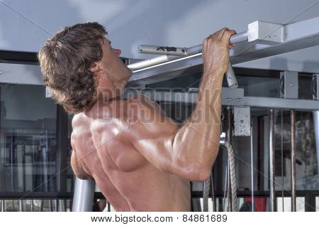 Profile and rear torso of muscular shirtless male Caucasian athlete performing pullups in gym poster