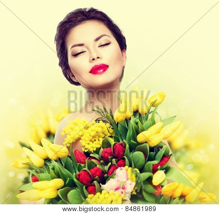 Beauty model Woman with Spring Flower bouquet. Beautiful girl with a Bouquet of colorful Tulip flowers. Happy surprised model woman smelling flowers. Mother's Day. Springtime